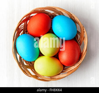 Easter eggs in a wicker basket on white background, top view - Stock Photo