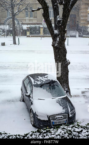 Parked car on pavement and snow in town, Strasbourg, Alsace, France - Stock Photo