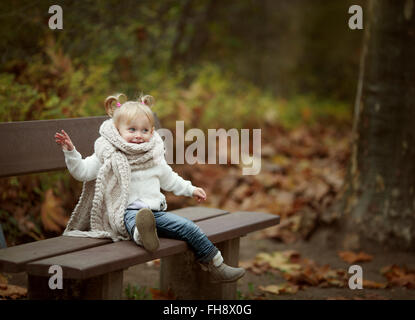 Blond little girl wearing big scarf sitting on a bench in autumn forest - Stock Photo