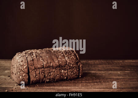 a sliced loaf of rye bread topped with sunflower seeds on a rustic wooden surface, in sepia toning - Stock Photo