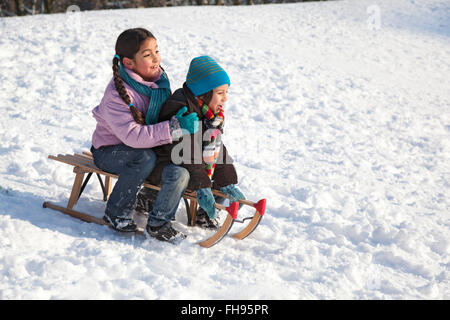 Two children on a sled having fun in the snow - Stock Photo
