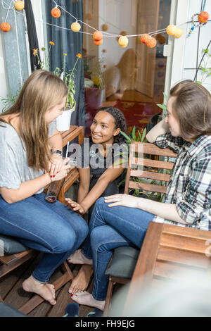 Three teenage girls sitting on a balcony talking and smiling - Stock Photo