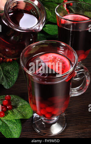 A glass of hot low-alcohol drink made from honey, cranberries, lemon - Stock Photo