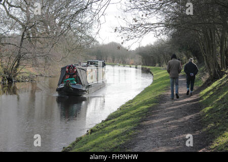 On a winters day two wrapped up walkers pass a narrowboat on The Leeds and Liverpool canal in Lancashire - Stock Photo