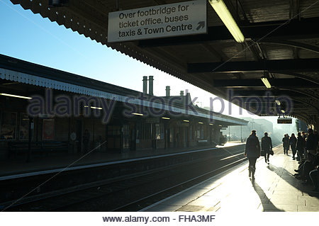 Early morning commuters wait for their train at Stroud railway station in the winter sunshine. Stroud, Gloucestershire, - Stock Photo