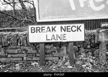 Break Neck Lane road sign in front of low stone wall - Stock Photo