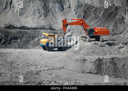 Excavator loading mining truck - Stock Photo