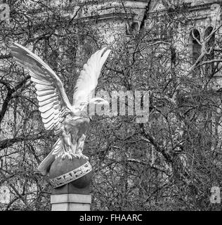 Statue of golden eagle with talons grasping ball with Ministry of Defence building in back ground - Stock Photo