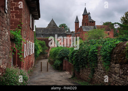 View on a path towards the tower of the church in red stone in the red village Collonges-la-Rouge in Dordogne area, - Stock Photo