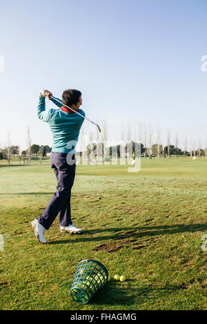 Golfer hitting a golf ball in the driving range of a golf club - Stock Photo