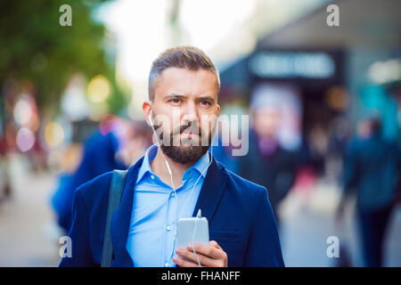 Manager with smartphone listening music outside in the street - Stock Photo