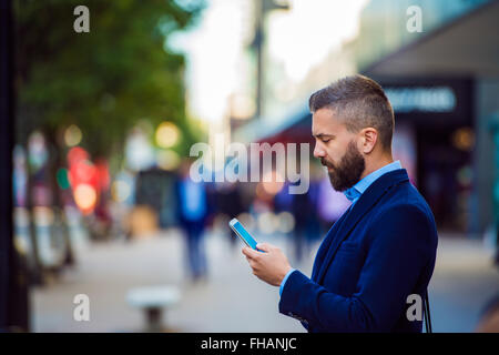 Hipster manager holding smartphone, texting outside in the stree - Stock Photo