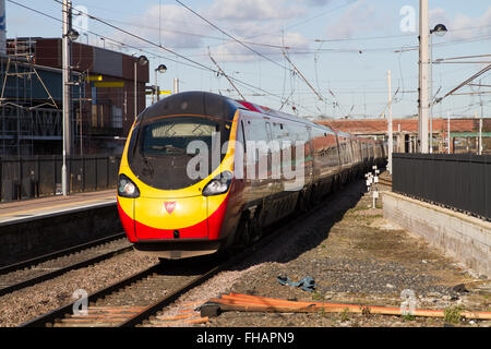 Virgin Trains Pendolino Arrives at Warrington Bank Quay with a Glasgow Euston service in bright sunlight - Stock Photo
