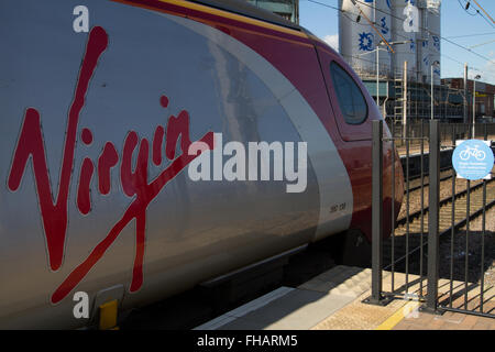 Virgin Pendolino Train at the cycle loading point at Warrington Bank Quay in bright sunlight, Unilever factory behind. - Stock Photo