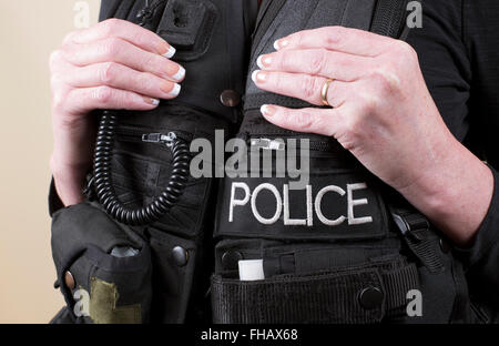 Married female police officer wearing a tactical vest - Stock Photo
