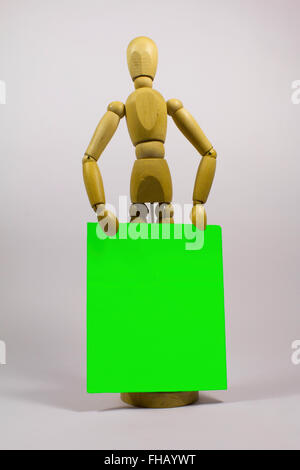 Artists mannequin holding green screen placard - Stock Photo