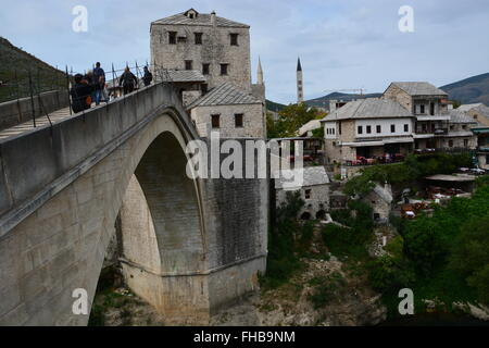 People cross the rebuilt 16th Century Ottoman bridge Stari Most or old bridge in Mostar. - Stock Photo