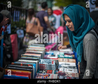 Muslim woman looking at radical political literature, rally for Gaza, London, Aug 9, 2014 - Stock Photo