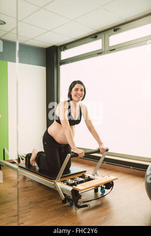 Pregnant woman doing Pilates exercises in a gym, with a reformer pilates machine, reflected in a mirror - Stock Photo