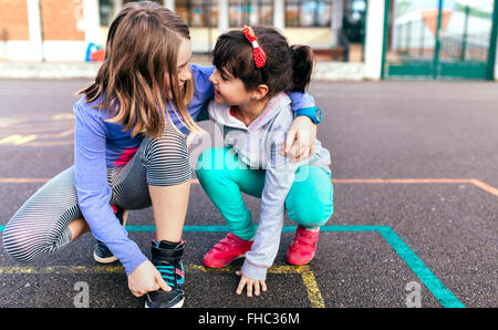 Two little girls playing together on the street - Stock Photo