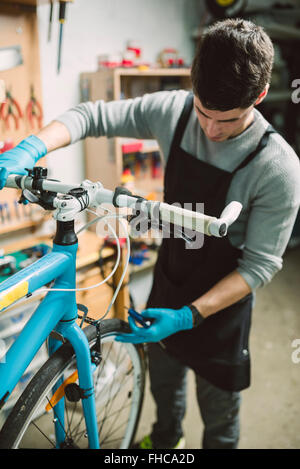 Mechanic repairing a bicycle in his workshop - Stock Photo