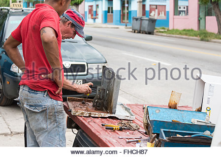 Cuban man repairing air conditioner in the street. A repairer is working on AC to make it work. Due to economic - Stock Photo