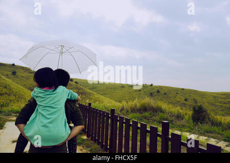 Daughter on Father's Back take umbrella ,Girl on father's back take umbrella,Father giving young daughter piggyback - Stock Photo