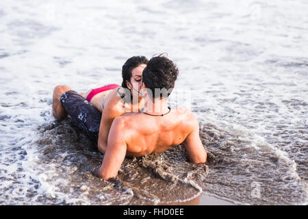 Couple in love kissing in the sea - Stock Photo