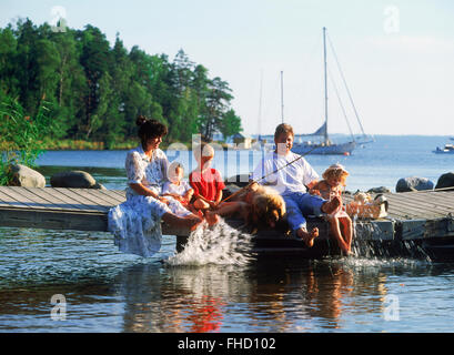 Dad and Mom with three kids and family dog sitting on lakeside pier during fishing picnic in Sweden - Stock Photo