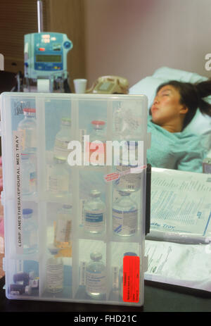 Woman connected to IV tubes in hospital recovery room with a menu of drugs - Stock Photo