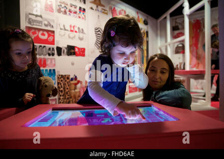 Milan, Italy. 24th Feb, 2016. A girl plays a game to match clothes and organize the wardrobe for Barbie at the exhibition - Stock Photo