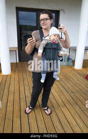 Multitasking mom with wine in one hand and cell phone in the other carrying Jack in a Babybjorn carrier. Zawady - Stock Photo