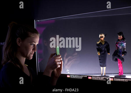 Milan, Italy. 24th Feb, 2016. A woman takes a photo for Barbie dolls at the exhibition 'Barbie-the Icon' in Milan, - Stock Photo