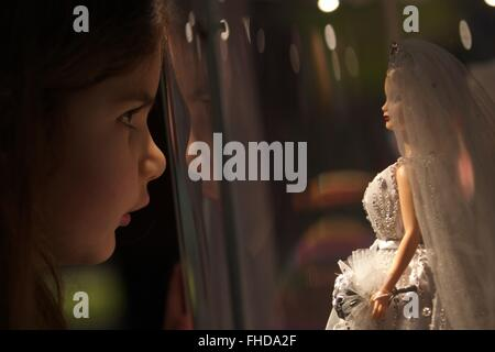 Milan, Italy. 24th Feb, 2016. A girl looks at a Barbie doll at the exhibition 'Barbie-the Icon' in Milan, Italy, - Stock Photo