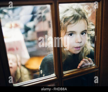 Portrait of little girl looking through a glass pane of a door - Stock Photo