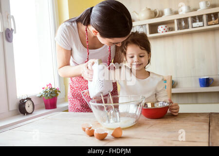Portrait of smiling little girl and her mother baking together - Stock Photo