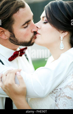 Bride and groom kissing. Wedding couple, newlyweds kiss. Close portrait. The man in bow tie with suspenders. - Stock Photo