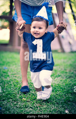 Portrait of baby boy at his first birthday holding by his mother's hands - Stock Photo