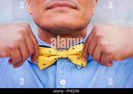 Mature man tying bow tie, close up - Stock Photo