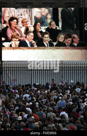 Crowds outside Buckingham Palace watch a broadcast of a rock concert held in Buckingham Palace's grounds to celebrate - Stock Photo