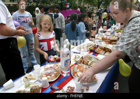 Revellers enjoying a special buffet at a Golden Jubilee street party in Jubilee Street in the Stepney Green area - Stock Photo