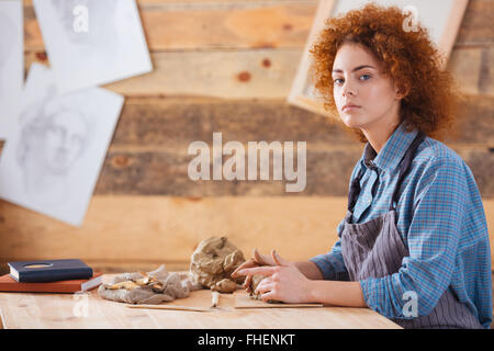 Pretty young woman potter with curly red hair sitting and working in pottery studio - Stock Photo