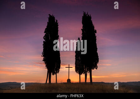 Sunrise in Tuscany, Val D'Orcia: famous cypress trees and a cross in silhouettes - Stock Photo