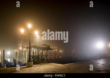 Canal with gondolas in the fog by night, Venice, Veneto, Italy - Stock Photo