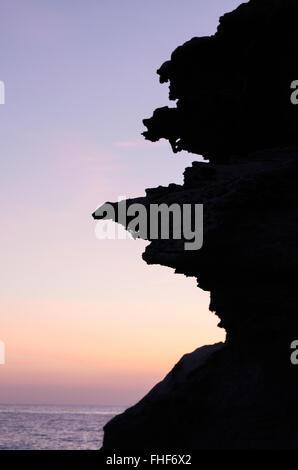 The volcanic rock formations in silhouette at sunrise on the beach Los Escullos, Cabo de Gata National Park, Almeria, - Stock Photo