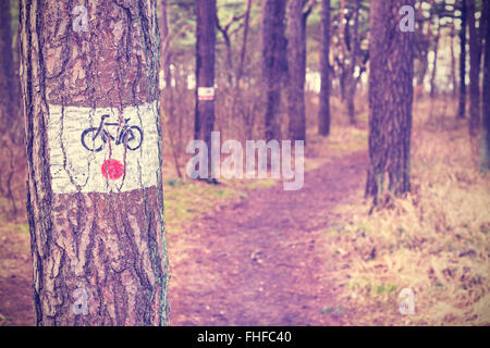 Vintage toned bike trail sign painted on a tree in forest, shallow depth of field. - Stock Photo