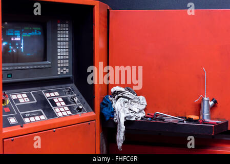 close-up of the control panel of an industrial machinery, painted in red, with buttons and knobs and a screen - Stock Photo