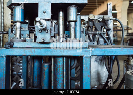close-up of an old, worn out, blue painted, hydraulic machinery, with oiled pistons and pressure dials, black hoses - Stock Photo