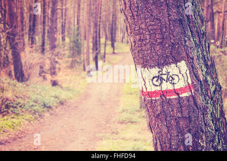 Vintage toned bike trail sign painted on a tree in forest. - Stock Photo