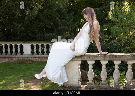Lady sitting on balustrade in the shade - Stock Photo